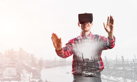 Guy wearing checked shirt and virtual mask stretching hands and trying to concentrate Stock Photos