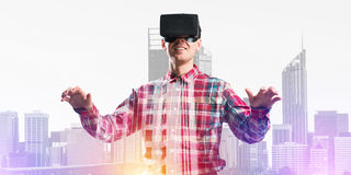 Guy wearing checked shirt and virtual mask stretching hands and trying to concentrate Stock Image