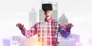 Guy wearing checked shirt and virtual mask stretching hands and trying to concentrate Royalty Free Stock Photography