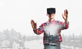 Guy wearing checked shirt and virtual mask stretching hands and trying to concentrate Royalty Free Stock Images