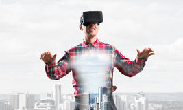 Guy wearing checked shirt and virtual mask stretching hands and trying to concentrate Stock Photo
