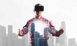 Guy wearing checked shirt and virtual mask stretching hands and trying to concentrate Royalty Free Stock Image