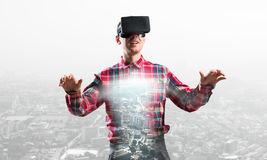 Guy wearing checked shirt and virtual mask stretching hands and trying to concentrate Stock Photography