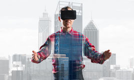 Guy wearing checked shirt and virtual mask stretching hands and trying to concentrate Stock Images