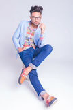 Guy wearing glasses and jeans posing seated Stock Photos