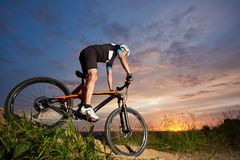 Guy wearing helmet and sportswear on mountain bike coming down the hill at sunset stock image