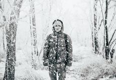 A guy wearing a jacket with a hood is standing in a snowy forest, snow is falling on him from above. Black and white royalty free stock image