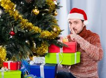 Man wearing Santa puts gifts under the Christmas tree Stock Image