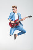 Guy wearing sunglasses jumping in studio while playing guitar Stock Images