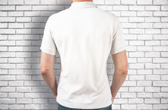 Guy wearing white shirt back. Back view of guy wearing empty white shirt on brick background. Retail concept. Mock up Stock Image