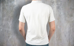 Guy wearing white shirt back. Back view of guy wearing empty white shirt on concrete background. Retail concept. Mock up Stock Photo