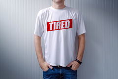 Guy wearing white t-shirt with label Tired printed on chest stock photography