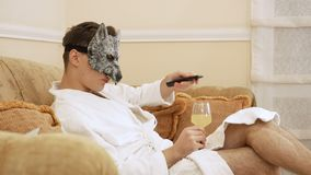 Guy wearing wolf mask looks tv and change the channels with remote control. Guy wearing wolf mask looks tv and change the chanels with remote control. The male stock video footage