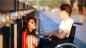 Guy On The Wheelchair Says algo à menina ruivo e à ela Iistens com cuidado, no passeio na noite do verão vídeos de arquivo