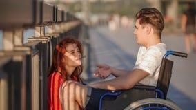 Guy On The Wheelchair Says qualcosa alla ragazza dai capelli rossi ed alla lei Iistens con attenzione, su passeggiata nella sera  immagini stock libere da diritti