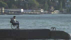 Guy In Wheelchair Throws Stones in acqua archivi video