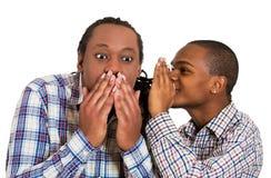 Guy whispering into man's ear, men spread rumor Stock Photo