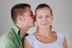 A guy whispering something to a girl Royalty Free Stock Photos