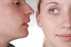 A guy whispering something to a girl. A guy whispering something strange to a girl Stock Photos