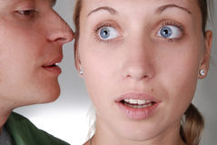 A guy whispering something to a girl Royalty Free Stock Photography