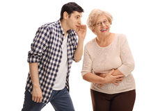 Guy whispering something to his grandma. Young guy whispering something to his grandma isolated on white background Stock Image