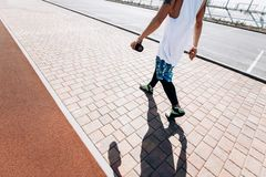 Guy with white headband, dressed in the white t-shirt, black leggings and blue shorts is walking along the sidewalk on stock images