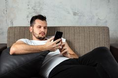 The guy in the white shirt is lying on the couch and sitting in the phone. The concept of laziness, apathy. Frustration, procrastination, the person at home royalty free stock images