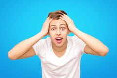 Guy in white in a white T-shirt holding his head, isolated on a blue background royalty free stock images