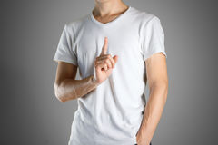 The guy in white t-shirt pointing finger up. Specifies the direc Stock Image