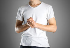 The guy in white t-shirt rubs hand in hand. Rubs the palm of your hand. Isolated.  royalty free stock photos