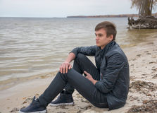 The guy who is sitting on the shore of the sea of autumn Royalty Free Stock Photography