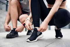 Guy and woman tying their shoelaces Stock Photos