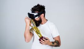 Guy won virtual competition and carries on shoulder goblet. Hipster on grateful face kisses goblet. Man with beard in. Virtual reality glasses is winner, grey stock photography