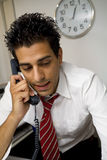 Guy at work. Young businessman talking on the phone in his office stock photo