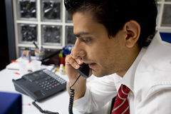 Guy at work. Young businessman talking on the phone in his office Royalty Free Stock Images