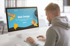 Guy work on modern web site on computer in graphic, web design studio office. Concept stock image