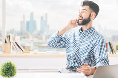 Guy at work talking on phone. Cheerful caucasian guy sitting at workplace and talking on cellular phone Royalty Free Stock Photos