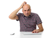 Guy working on a computer and scratching his head Stock Photo