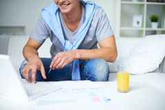 Guy working. Image of young guy in casual sitting on sofa and using laptop Royalty Free Stock Photography