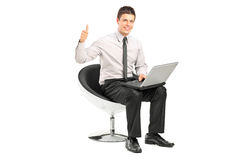 Guy working on laptop and giving thumb up stock image