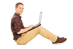 Guy working on laptop seated on the floor Stock Images