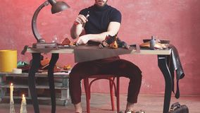 Guy working with leather using crafting tool at workshop. stock video footage