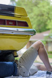 Guy working under classic muscle car in driveway outside. Young man laying on ground underneath hot rod fixing car on sunny day stock photo