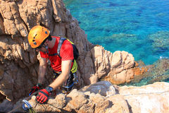 Guy working in a via ferratas over the sea. In summer Royalty Free Stock Photo