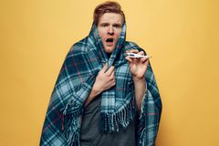 Guy Wrapped in Plaid Pointing on Thermometer stock photo