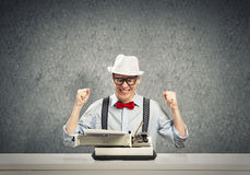 Guy writer. Young guy writer in hat and glasses using typing machine stock photos