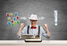 Guy writer. Young guy writer in hat and glasses using typing machine royalty free stock photography