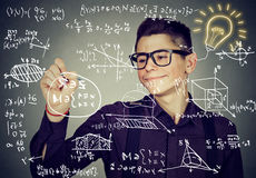 Guy writing high school maths and science formulas. Smart guy writing high school maths and science formulas on blackboard Stock Images