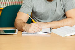 Guy writing in his desk Stock Images