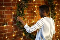 Guy with xmas wreath. African-american guy in casual striped pullover standing by brick wall and decorating it with coniferous xmas wreath stock image